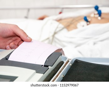 Doctor with electrocardiogram equipment making cardiogram test