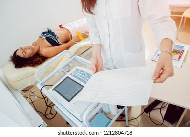 Doctor with electrocardiogram equipment making cardiogram test to patient in clinic. Diagnostic, healthcare, medical service