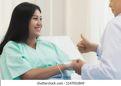 Doctor encouraging patient during treatment therapy and holding hands to support.