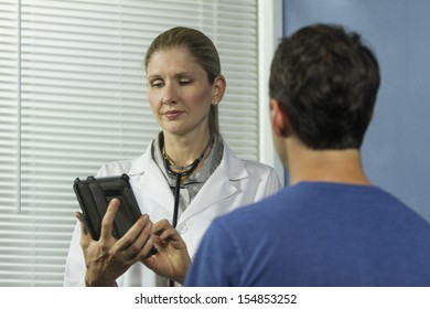 Doctor entering information into tablet while with patient, horizontal
