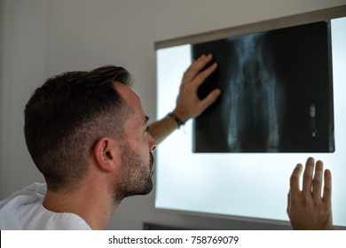 The doctor is evaluating the condition by looking at the x-ray.