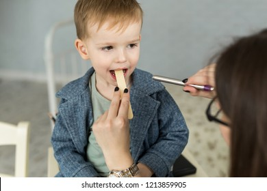 Doctor examine child's throat. Boy at pediatrician office.