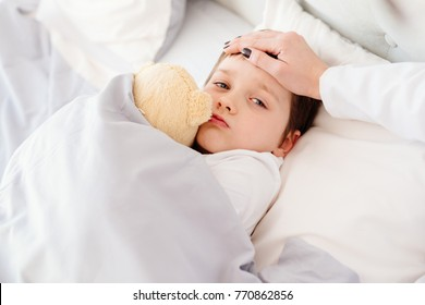 Doctor examines child fever with hand on forehead. Sick eight years boy in bed
