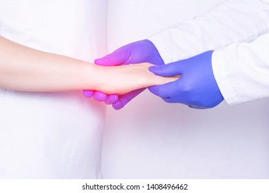 Doctor examines a girl's wrist joint for sprain, inflammation and pain in her wrist, close-up, chronic pain, ankylosing spondylitis