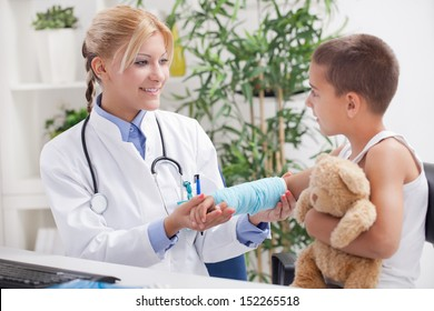 doctor examines an injured hand a little boy in office