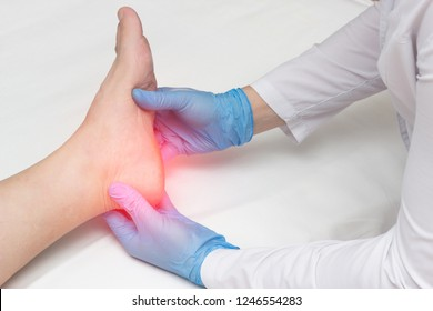 Doctor examines the leg of the woman's heel for heel spurs, pain in the foot, plantar fasciitis, osteophyte