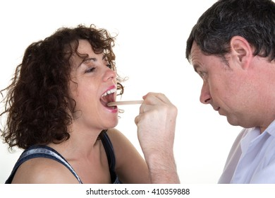 Doctor examines middle aged woman for sore throat