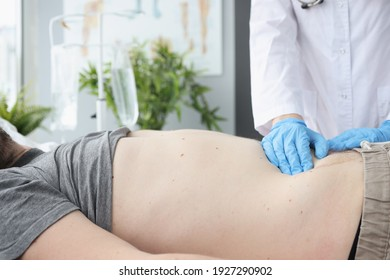 Doctor examines patient's abdomen on couch. Bowel disease and indigestion concept