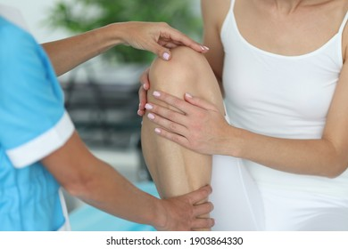 Doctor examines patient's leg in the office. Knee injury concept