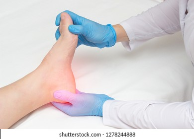 Doctor examines the sore heel of a woman who has a heel spur, orthopedist
