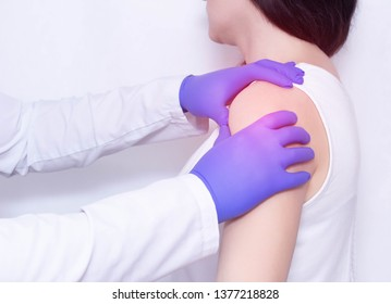 A doctor examines the sore shoulder of a patient with inflammation and stiffness in the shoulder joint, polymyalgia, ankylosing spondylitis