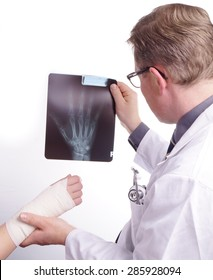 The doctor examines an X-ray picture , while the patient's sprained hand resting in his hand