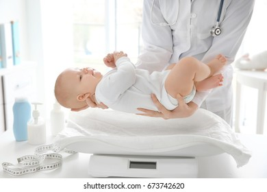 Doctor examining baby on scales in room