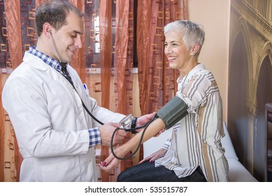 Doctor examining blood pressure and heart rate on a senior, older woman in a clinic