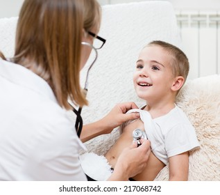 doctor examining boy with stethoscope