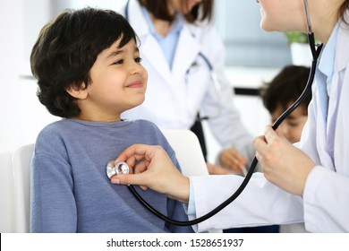 Doctor examining a child patient by stethoscope. Cute arab boy at physician appointment. Medicine and healthcare concept