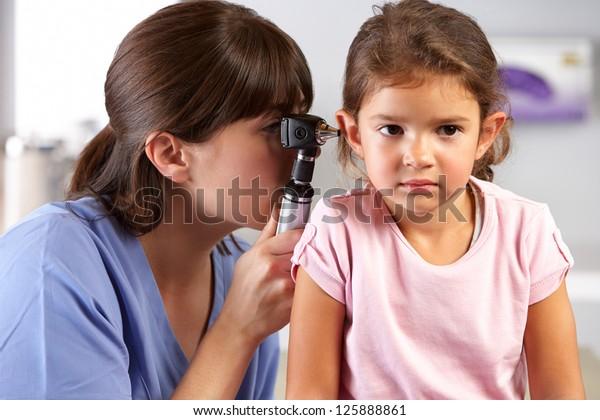 Dokter onderzoekt de oren van het kind in het kantoor van de dokter