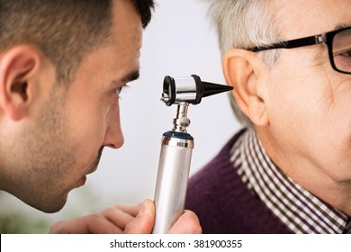 Doctor Examining Ear of a old patient, close up