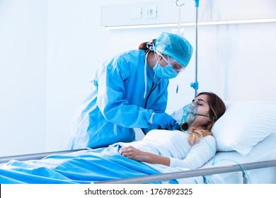 Ärztin, die weibliche Patientin unter kritischen Gesundheitsbedingungen mit einem Stethoskop in der Intensivstation eines modernen Krankenhauses während einer Covid-19-Pandemie untersucht