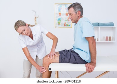 Doctor examining her patient knee in medical office