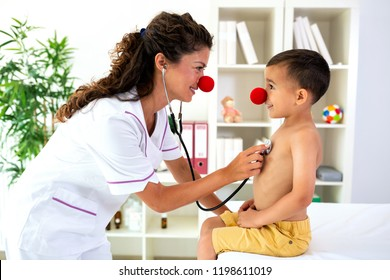 Doctor examining her patient with stethoscope, while they are both wearing a clown's nose