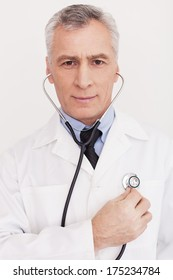 Doctor examining himself. Cheerful grey hair doctor in white uniform examining himself with stethoscope and looking at camera while standing isolated on white