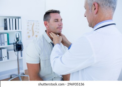 Doctor examining his patient neck in medical office