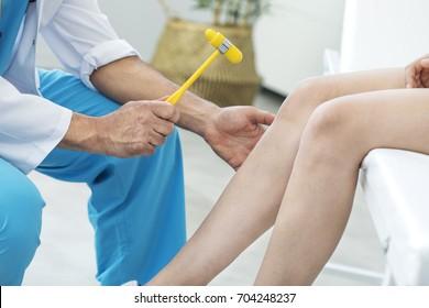Doctor examining the knee reflex