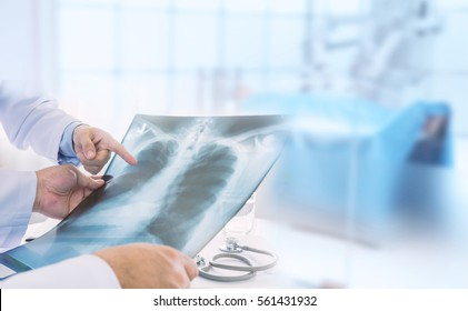 Doctor examining at lungs radiograph x-ray film of patient in operation room. medical concept.
