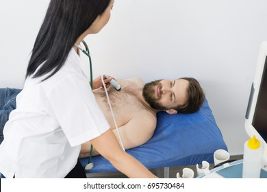 Doctor Examining Male Patient With Ultrasound Machine