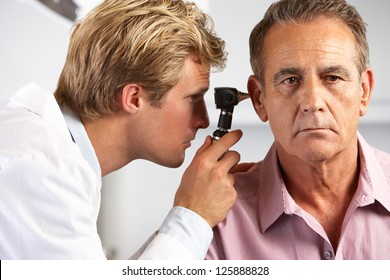 Doctor Examining Male Patient's Ears