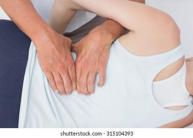 Doctor examining man back in medical office