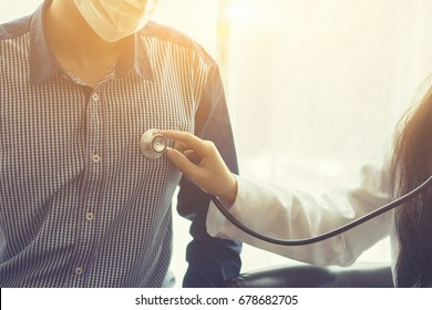 Doctor examining a man patient by stethoscope. Medicine and medical health care concept.vintage color