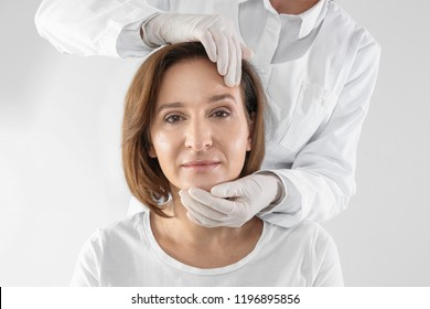 Doctor examining mature woman face before cosmetic surgery on white background