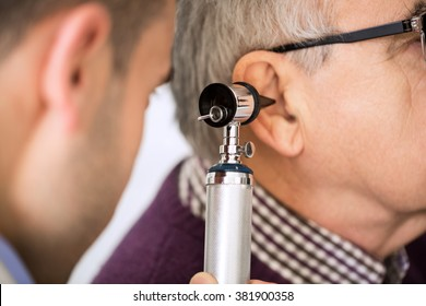 Doctor Examining old Patient's Ear
