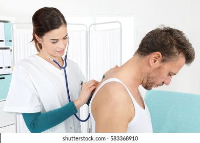 Doctor examining patient with stethoscope in medical office