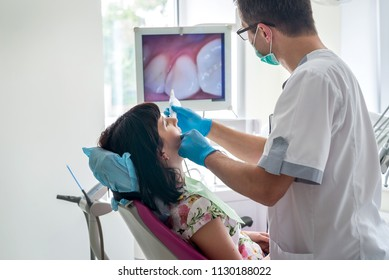 Doctor examining patient's teeth with intraoral camera