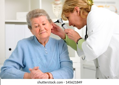 doctor examining senior patient's ears