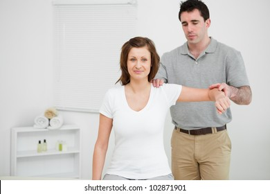 Doctor examining the shoulder of his patient while holding his arm in a room