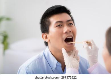 Doctor examining throat of patient with tongue depressor