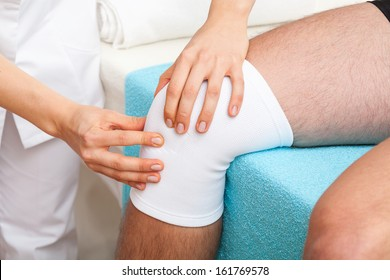 Doctor examining the twisted knee of patient