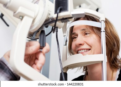 doctor examining woman's eyes with a measurement machine