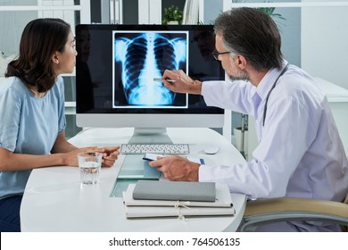 Doctor explaining lungs x-ray on computer screen to young patient