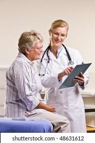 Ärztin, der älteren Frau eine Krankenkarte erklärt