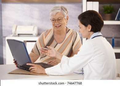 Doctor explaining results to senior patient in office, using laptop computer.?