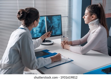 Doctor explaining a x-ray to the patient and pointing at the computer screen, the woman is wearing a cervical collar