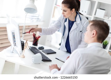 The doctor explains the problem to the patient on the computer.