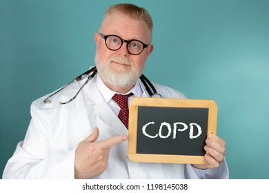 Doctor with eyeglasses holding with chalkboard COPD lettering on blue background