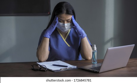 Doctor feels headache and stress due to constant lack of sleep and excessive workload. Tired woman in blue protective uniform sitting in front of computer in office sleepily massaging her head.