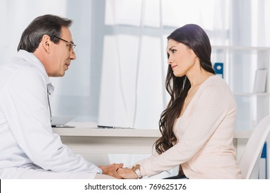doctor and female patient sitting and holding hands